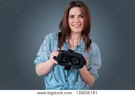 Excited young woman using a VR headset and experiencing virtual reality on grey blue background. She holds glasses for viewer