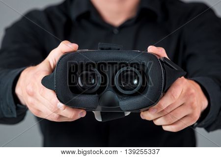 Excited young man using a VR headset and experiencing virtual reality on grey blue background. He holds glasses for viewer
