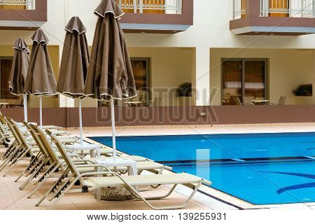 BALI GREECE - APRIL 29 2016: Empty sunbeds and umbrellas are at the pool empty without tourists early in morning. Relax and sunbathe by pool with clear blue water in Resort hotel Bali Crete Greece