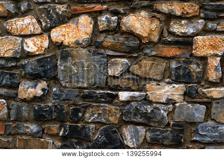 Stone texture of granite wall for the background. Dark monolithic stones joined with cement in a single stone panel. Greek architecture Bali Crete