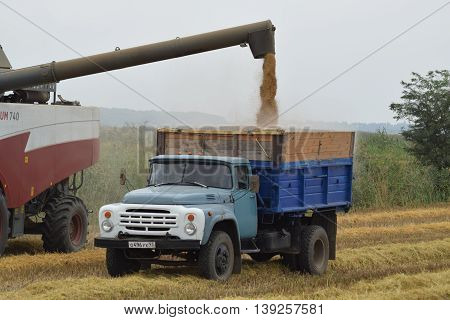 Unloading Grain From A Combine Into A Truck.