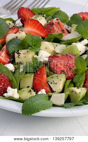 Salad spinach with strawberries avocado mint ricotta and sesamepoppy seeds