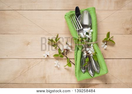 Spring table setting with cutlery napkin and flowers. Silverware in spring scenery.