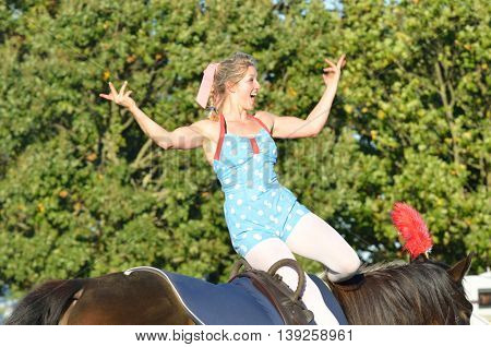 IPSWICH SUFFOLK UK 25 October 2014: East Anglia Equestrian Fair girl on horseback waving to crowd