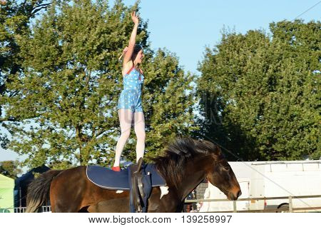 IPSWICH SUFFOLK UK 25 October 2014: East Anglia Equestrian Fair girl standing on horseback waving to crowd
