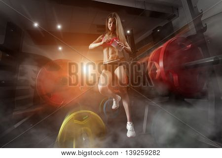 poster of Fitness woman standing in a smoky gym. Fitness woman in the gym. Fitness girl with shaker posing in the gym. Fitness - concept of healthy lifestyle. Perfect fitness body.