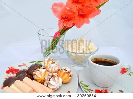 Sweets for the coffee - biscuits with condensed milk sprinkled with powdered sugar cubes and a cup of coffee