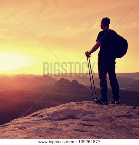 Man With Tourist Poles In Hand And Sporty Backpack Above Valley.