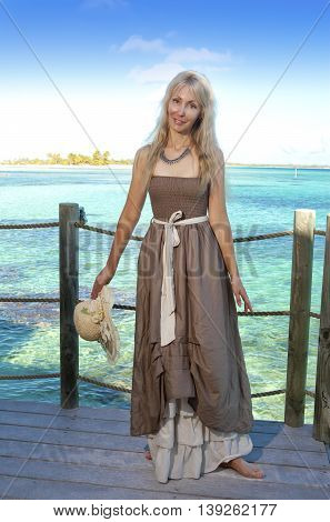 The beautiful woman in a long dress on a wooden platform over the sea