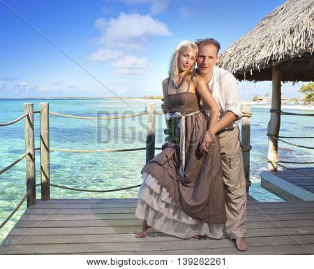 man gives a rose to the woman on the turquoise sea background