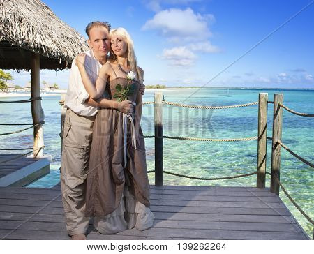 man gives a rose to the woman on the turquoise sea background.