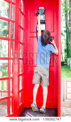 boy reaches to the telephone. child tries to call the red phone box. view from the back