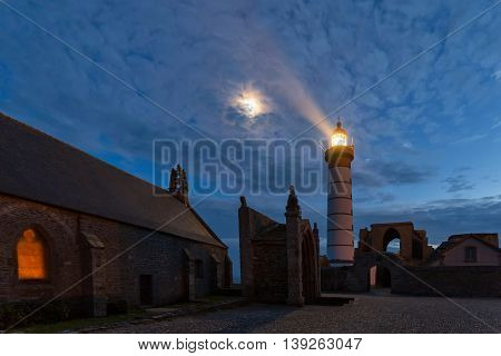 Mystical church and lighthouse illuminated with moon over cloudy sky at Saint Mathieu point, Brittany, France