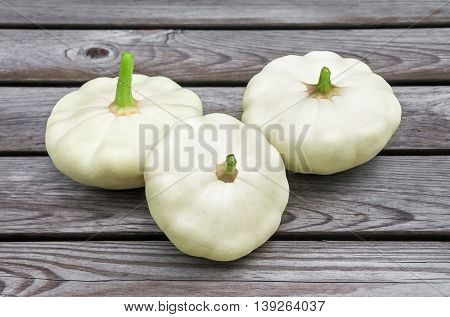 three raw squash on the wooden table