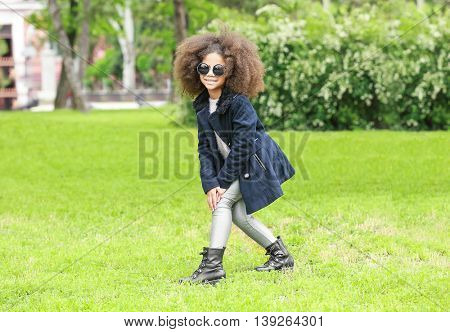 Afro American little girl wearing stylish clothes outdoors. Fashion kid concept