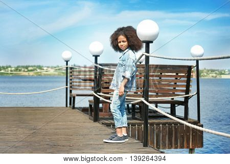African American  little girl wearing denim clothes outdoors. Fashion kid concept