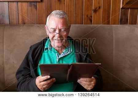 Senior Man Reading A Restaurant Menu