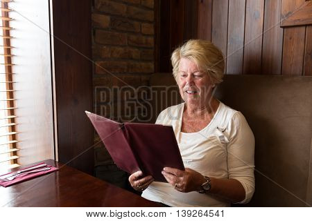 Senior Woman Reading A Restaurant Menu