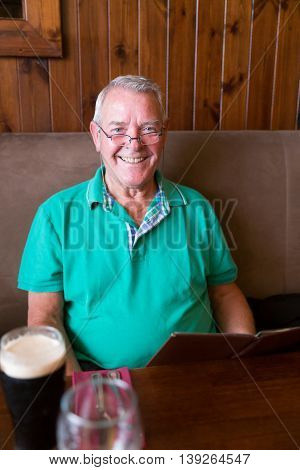 Smiling Senior Man Holding A Restaurant Menu