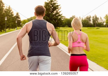 Back View Portrait Of Muscular Man And Slim Woman Running On Track