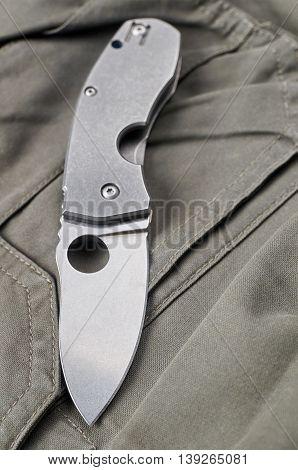 Folding knife on a grey, khaki background