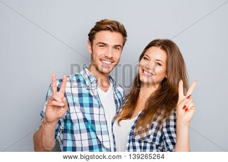 Cheerful Happy Young Couple Showing Two Fingers