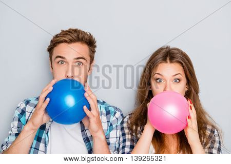 Portrait Of Happy Young  Man And Woman Inflating Balloons