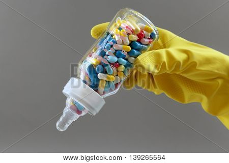 Hand in glove holding feeding bottle full of pills on gray background