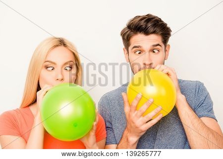 Two Funny Lovers Inflating Balloons For Celebration And Grimacing