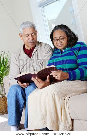 Couple reading the bible in their home
