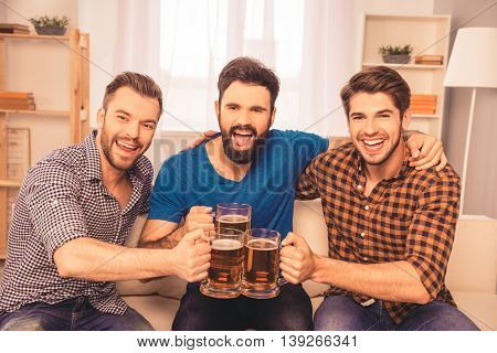 Cheers! Photo Of Handsome Men Celebrating Victory And Clinking Glass Of Beer