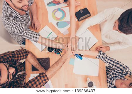 Top View Of Happy Business Team Putting Their Hands On Top Of Each Other At Conference