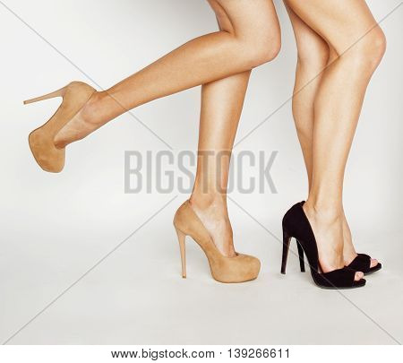 two pairs of female legs in high heels shoes isolated on white background close up