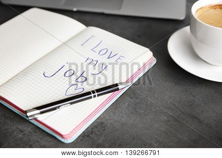 I love my job concept. Open notebook on office table