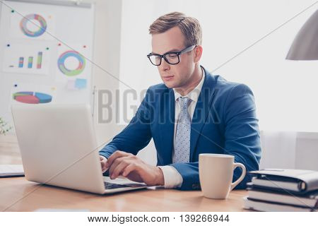 Concentrated  Smart Businessman In Glasses Working In Office With Laptop