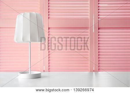 Stylish lamp on pink folding screen background