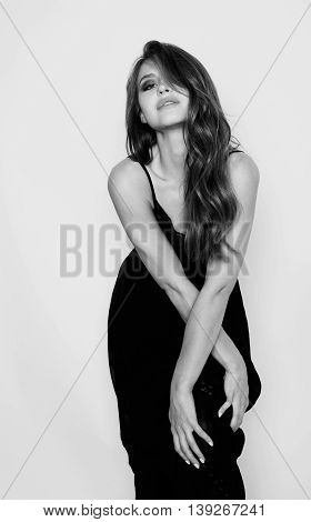 young brunette pretty woman in black dress posing on white background with make up sexy closeup