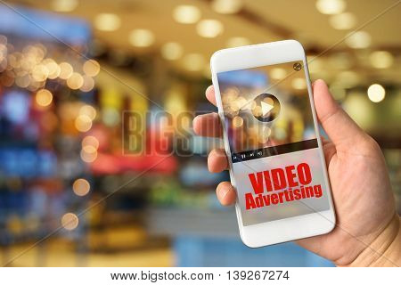 Woman hand holding smartphone against blur bokeh of shop background VIDEO Advertising concept