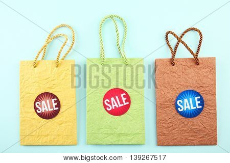 Paper bags with word sale on blue background