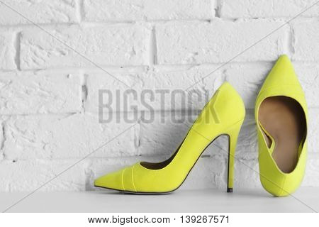 Yellow woman high heels on a brick wall background