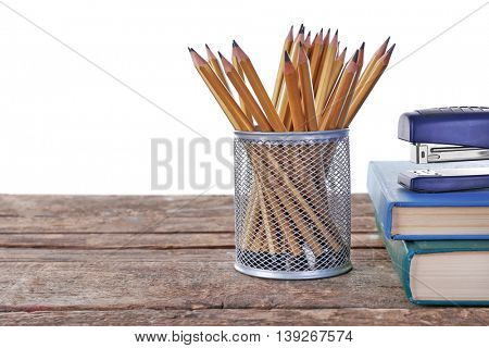 Composition with pencils in metal holder on white background