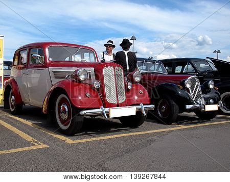 Gangsters and their cars.  Lodz, Poland - June 19, 2016 Retro cars from the 30s of the twentieth century, Opel and Cirtoen and men dressed as American gangsters in the exhibition of old cars in Lodz.
