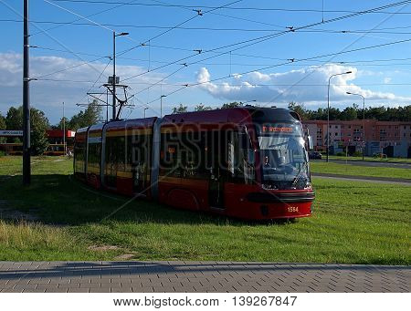 Tram from Lodz.  Lodz, Poland - July 20, 2016 Modern tram on the trail in Lodz, expected before the intersection on a green light.