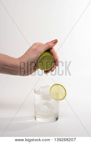 Female hand squeezing lime into glass cocktail