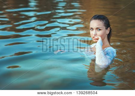 Portrait of a woman in a white dress her face wet because it is in the water.