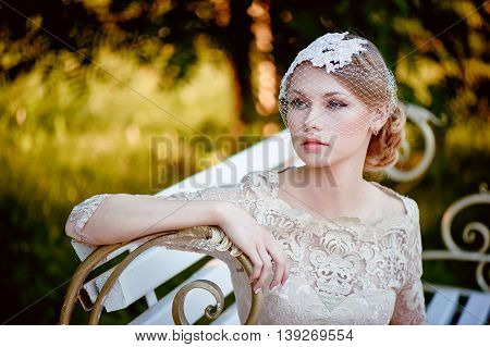 Beautiful young blonde with a hairstyle and veil sitting on a bench, romantic looks