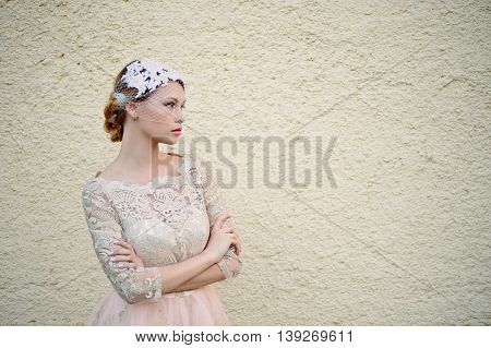 Beautiful young blonde with a hairstyle and veil is against a background of solid sand wall, neutral colors, pastel and romantic looks