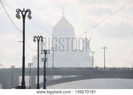 Patriarchal bridge, lanterns, Christ Savior Cathedral in fog in Moscow, Russia