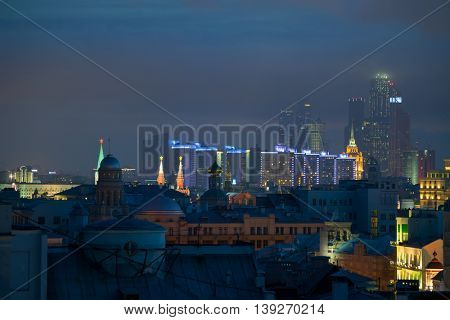 Stars on Kremlin towers, skyscrapers and buildings of New Arbat Street in center of Moscow, Russia at night