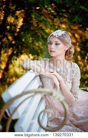 Beautiful blonde with a hairstyle and veil sitting on bench, romantic looks